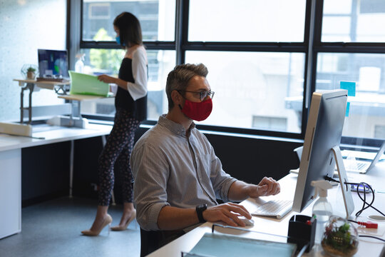 Caucasian man wearing face mask using computer while sitting on his desk at modern office