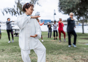 Mature chinese woman do tai chi with blirred group of people outdoor in the park
