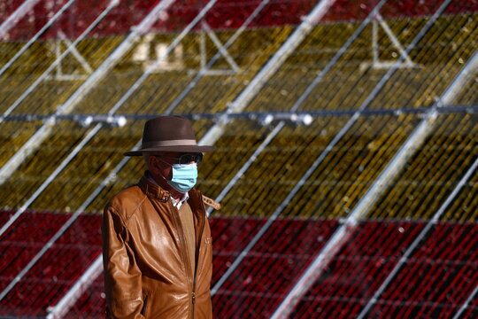 A man wearing a single-use protective mask walks past a Christmas decoration in the colours of the Spanish flag in Madrid