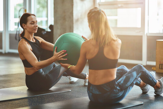 Working out together. Two young athletic women in sportswear exercising with ball at gym