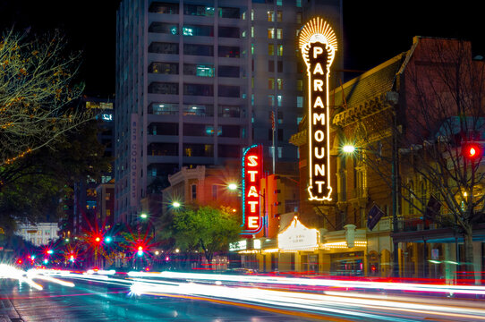 Austin, TX--Jan 9, 2019; time exposure of car lights streaking past the Paramount and State theaters, music venues, in downtown Texas state capital illuminated by neon marque signs at dusk