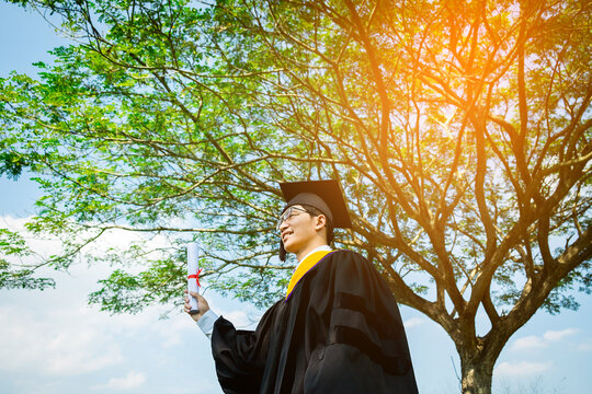 Low Angle View Of Man In Graduation Gown Standing Against Tree
