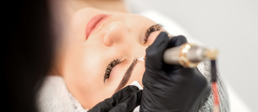 Beautician applying permanent makeup on eyebrows of young woman by special tattoo machine tool