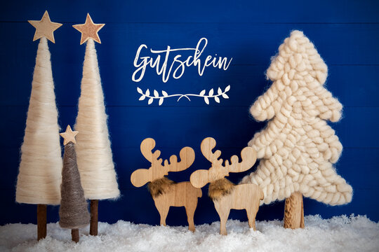 German Calligraphy Gutschein Means Voucher On Blue Background With Snow. Decoration And Ornament Like Christmas Trees And A Moose Couple.