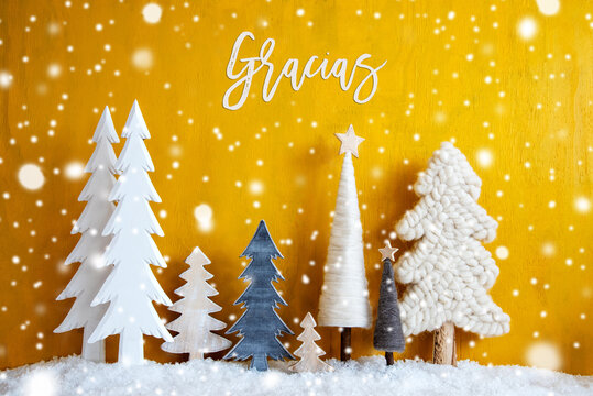 Christmas Trees With Spanish Calligraphy Gracias Means Thank You. Yellow Wooden Rustic Background With Snow And Snowflakes. Christmas Decoration With Stars.