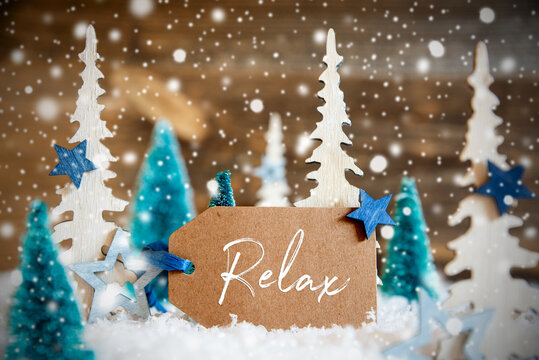 Label With English Text Relax. Christmas Trees With Star Decoration And Ornament. Brown Rustic Wooden Background With Snow And Snowflakes