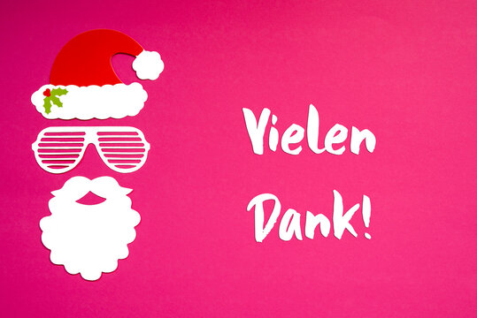German Text Danke Means Thank You. Santa Claus Paper Mask With Christmas Decoration And Accessories. Pink Paper Background