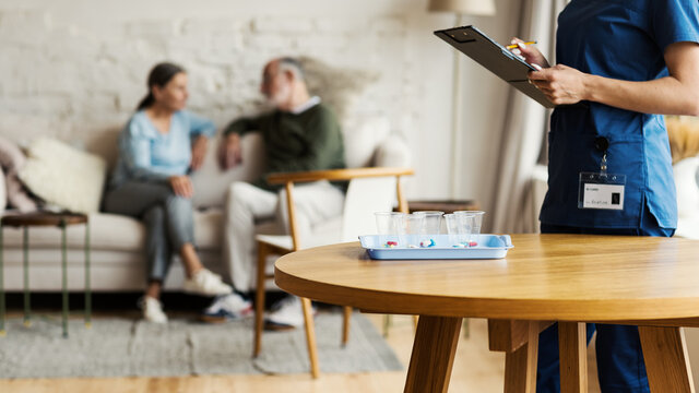 Unrecognizable young nurse making marks in list on clipboard while giving vitamin pills to senior patients in assisted living home, elderly couple talking on sofa in background