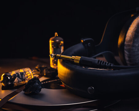 Closeup of golden headphone jack with headphones, tubes and magnetic tape in background