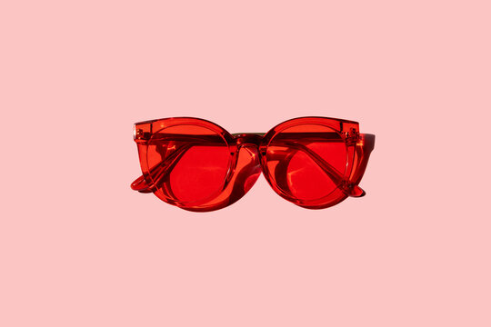 Trendy modern red sunglasses on pink background