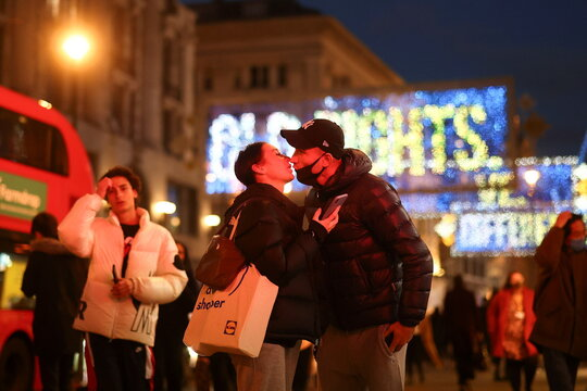 A couple kiss in front of Christmas lights on Oxford Street amid the coronavirus disease (COVID-19) outbreak in London