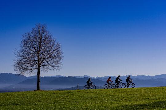 Urlaub in Oberbayern: Blaues Land mit Bergen im Hintergrund in der Nähe von Peißenberg - Fahradfahrer in der nachmittags Herbststimmung bei der Abfahrt vom Gipfel