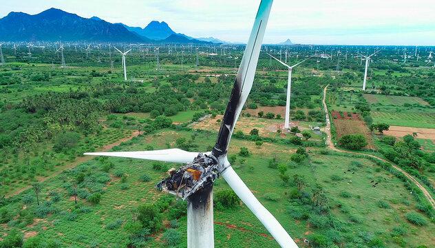 Aerial, close up view of wind turbine power plant Burned damaged wind turbine over blue sky.