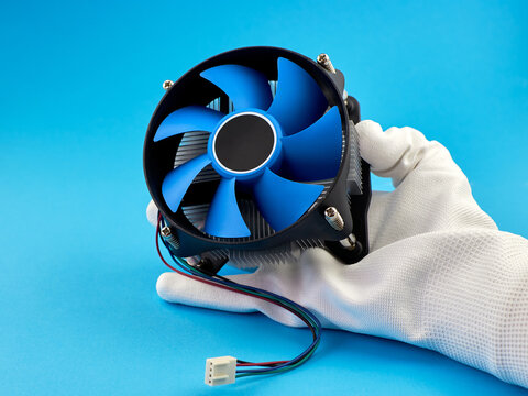 PC CPU cooler with thermal paste. A hand wearing a white glove holds the CPU cooler of the computer.