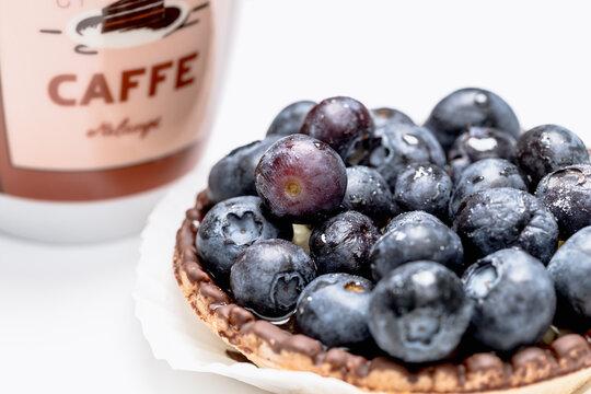 Close up einer Blaubeer Tartelette mit einer Kaffetasse vor weißem Hintergrund