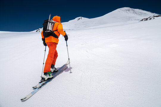 A mountaineer skier with a backpack, an ice ax, skis and poles, ascend on a ski tour to Mount Elbrus. Backcountry and freeride skiing concept