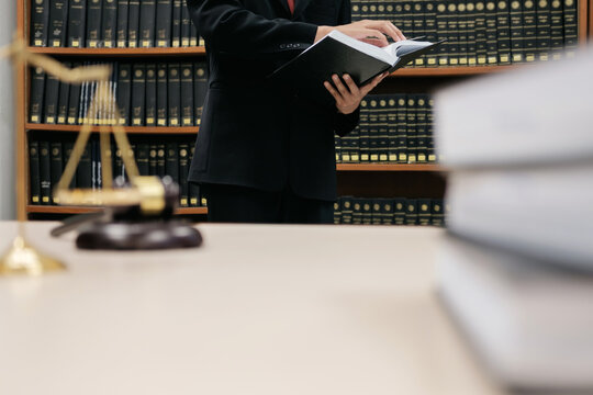 Midsection Of Lawyer Reading Book While Standing Against Bookshelf In Office