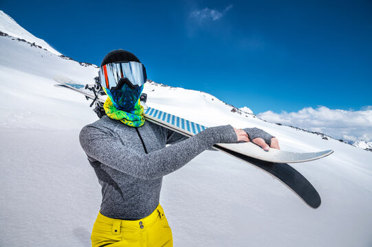 An attractive slender woman skier stands without a jacket high in the mountains and holds her skis on her shoulder against the background of high snow-capped peaks and clouds