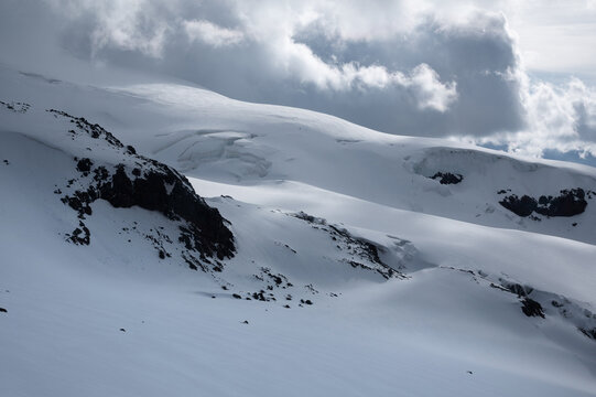 Rocky slopes with a glacier covered with snow in the evening with low clouds