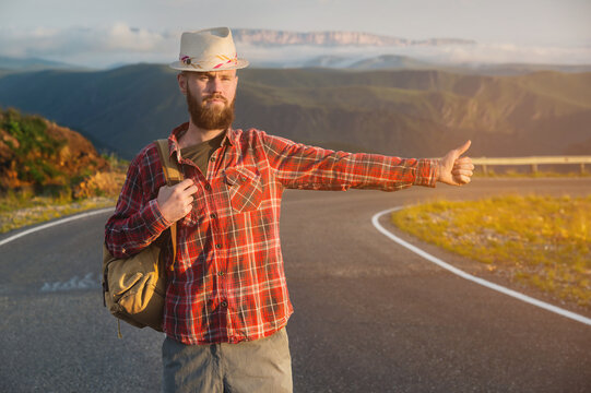 A bearded man hitchhiker in a hat and with a backpack stops an auto gesture while standing on a country road in the mountains at sunset