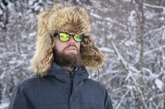 Attractive bearded man in sunglasses and a big fur hat on the background of a snowy forest in winter