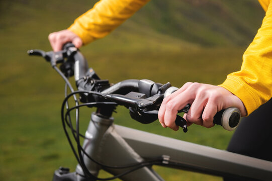 Close-up of woman cyclist hand on handlebars of mtb bike outdoors in mountains