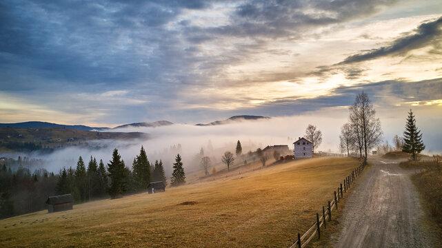 Alpine village. Autumn rural landscape. Cold November morning. Morning fog in mountain valley