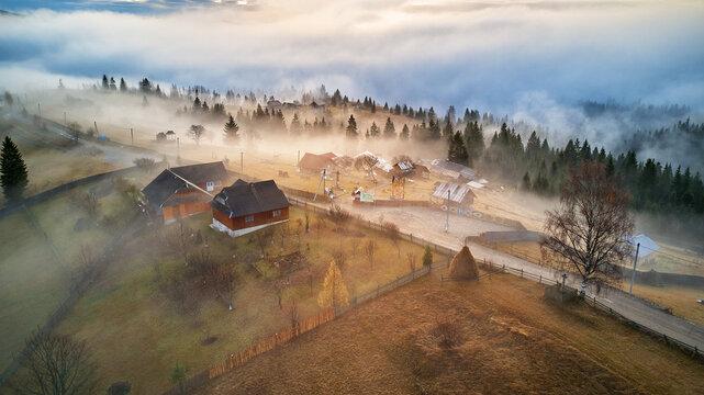 Alpine village. Autumn rural landscape. Cold November morning. Morning fog in mountain valley.