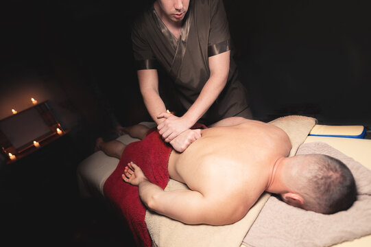 Male masseur doing back massage to client in dark room of massage spa
