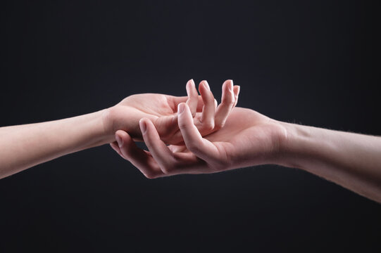 Two hands are holding each other. Symbol of tenderness, care and support by a man of a woman on a dark background