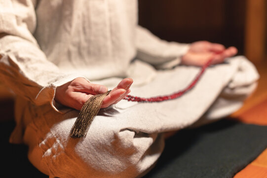 Close-up of a meditating practitioner's hand with a rosary in a dark room