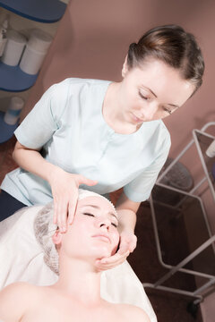 Professional masseur woman making facial massage to client in spa salon