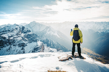 Climber take a mountain landscape photo on his smart phone. Hiker with backpack standing on top of a mountain and enjoying view. Tourist walk in the snow in the mountains during the winter holidays.