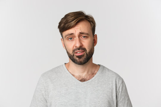 Skeptical and unamused bearded man in gray t-shirt, frowning and looking exhausted, standing over white background
