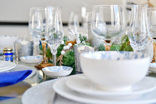 Christmas dinner and New Year celebration concept. Close up view white dishware blue napkins decoration on the table ready for quest reception, ornate table setting with candle and xmas wreath