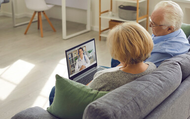 Senior couple sitting on couch with laptop and having video call with online doctor