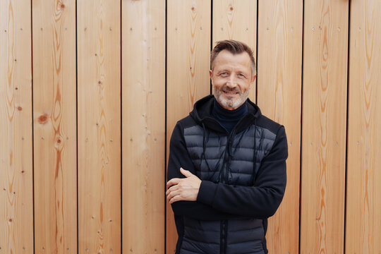 Trendy middle-aged man posing against a fence