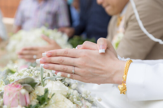 Cropped Image Of Bride With Hands Clasped Praying During Wedding Ceremony