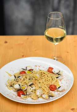 Italian cuisine, spaghetti pasta with vongole clams with glass of white wine