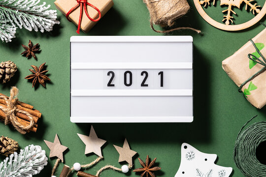 2021 on the lightbox with assortment of natural Eco friendly festive decorations on dark green background. New Year concept.