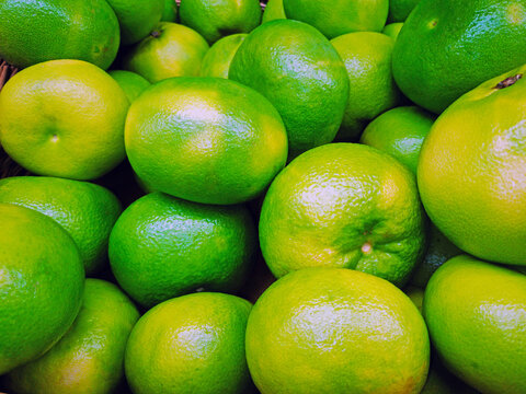 Group of green tangerines in the supermarket, Mandarin background, Fresh tangerines from the farm garden, a lot of tangerines in the market square. Healthy food concept.