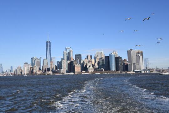Ein Blick auf den Big Apple in New York City von der Fahrt in Richtung Staten Island. Möwen begleiten die Fähre. Ein herrlicher Blick auf die Skyline von Manhattan.