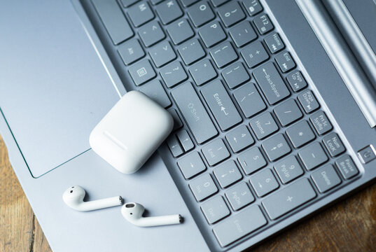Tilburg, Netherlands - 11.19.2020:  white Apple AirPods 2 with loading case on silver laptop keyboard at wooden table. Illustrative editorial photo.