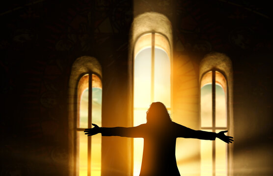 Silhouette of a woman praying inside a church with sunrise through the window background