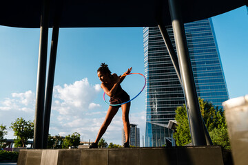 Sporty woman exercising with plastic hoops in modern city against blue sky Fotomurales