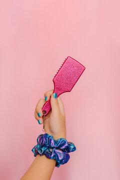 Hand of teenage girl holding pink hair brush