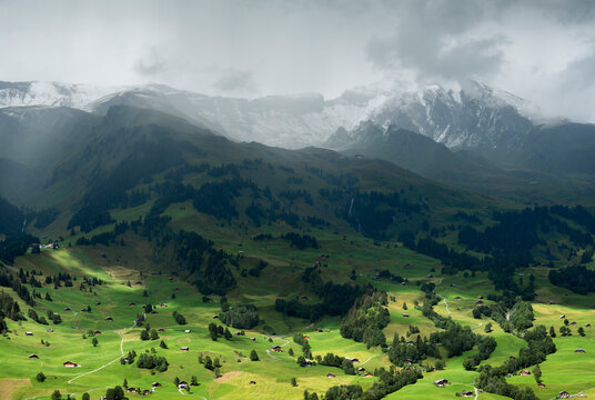 View of village of Grindelwald, Bern, Switzerland. Two glaciers reached the village of Grindelwald around 100 years ago, but due to climate change, they have retreated kilometres into the mountains. Clouds are constantly being formed around the mountain tops.