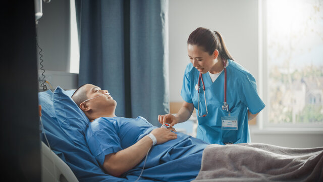 Hospital Ward: Friendly Chinese Head Nurse Checks Finger Heart Rate Monitor / Pulse oximeter Vital Signs of a Male Patient Resting in Bed. Nurse Helps Man Getting Better after Surgery.
