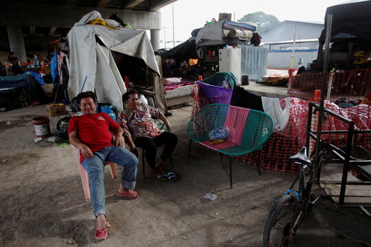 A couple sits next to their belongings under an overpass, where they are sheltered along other residents that lost their homes due to the floods caused by heavy rain brought by Storm Iota, in San Pedro Sula