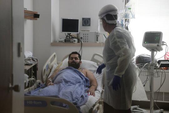 Registered nurse Jora Hovsepian, 52, helps patient Jairo Bonilla, 34, in the COVID-19 intensive care unit, as the global outbreak of the coronavirus disease (COVID-19) continues, at Providence Saint Joseph Medical Center in Burbank
